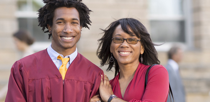 Student in graduation robe with parent.
